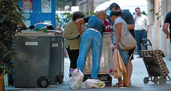 Personas cogiendo alimentos que un supermercado acaba de tirar a la basura